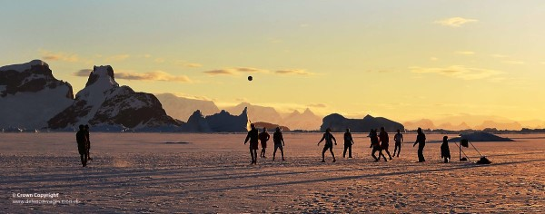 Members of HMS Protectors Ships Company, play football on the ice as the sun sets in Antarctica.